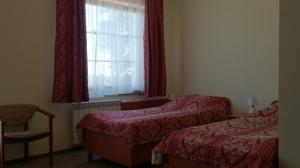 pokój z dwoma łóżkami, czerwone nakrycia, okno
