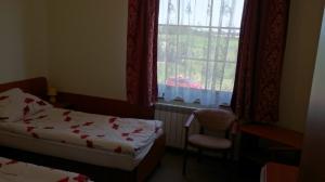 pokój z dwoma łóżkami, białe nakrycia w czerwone kwiatki